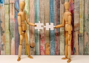 2 wooden model figures each holding a jigsaw piece and connecting them together