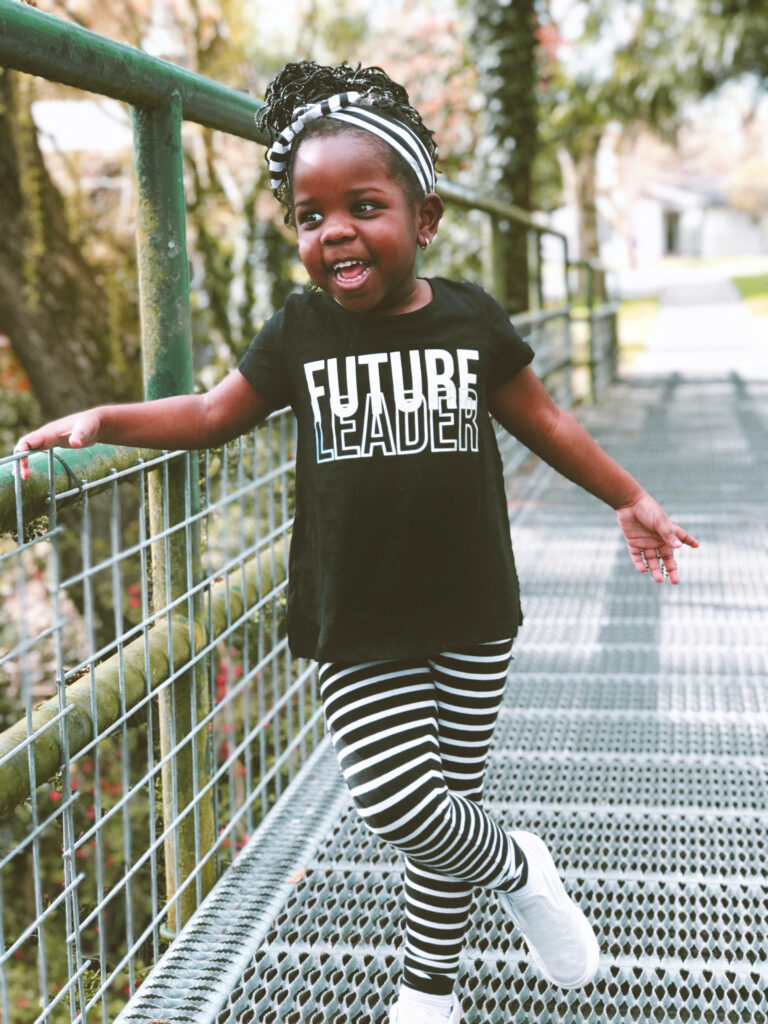 A little girl wearing a T-shirt that says Future Leader