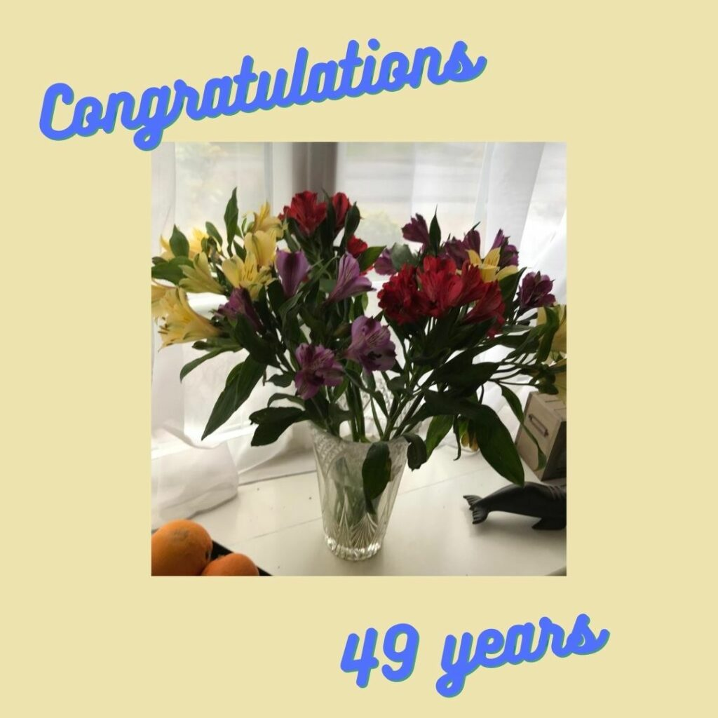 A photo of flowers with the word congratulations written above and 49 years below