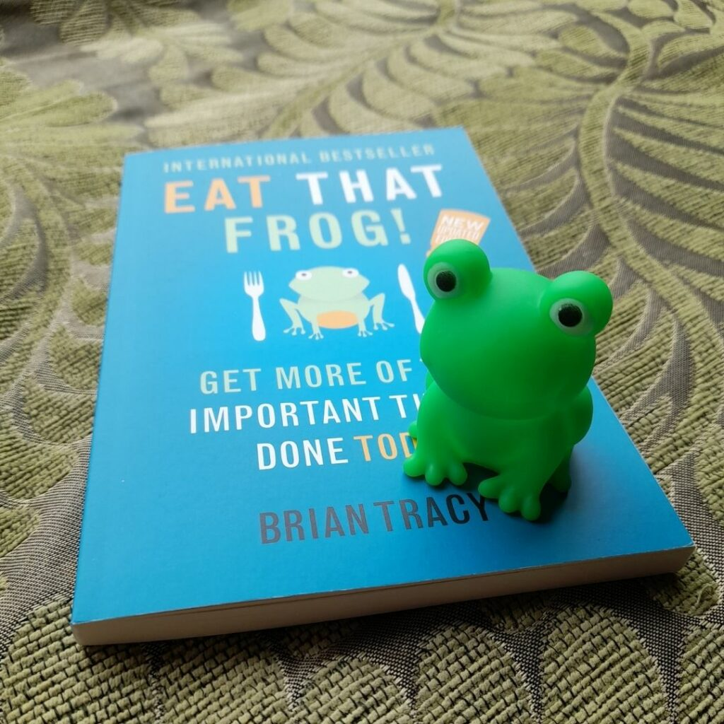 My thank you gift of a bright green frog toy sitting on top of the book Eat That Frog written by Brian Tracy
