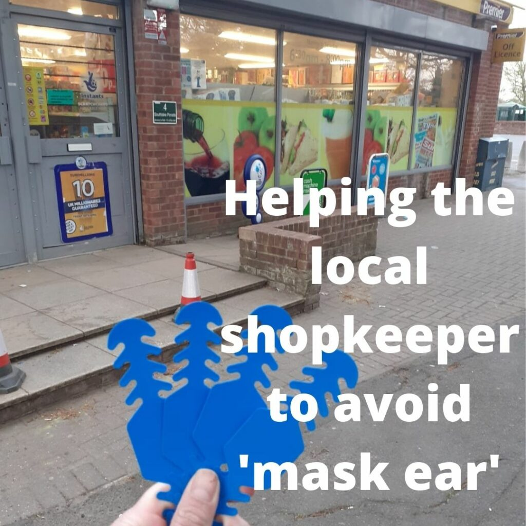 a hand holding some blue plastic strips in front of a corner shop window
