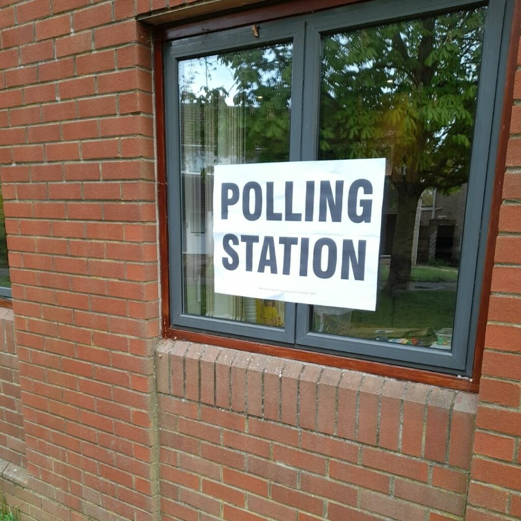 A photo of the words polling station stuck on a window