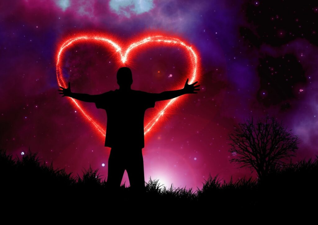 A person stands with arms outstretched in front of a moody night sky and a lit up heart shape of self-compassion