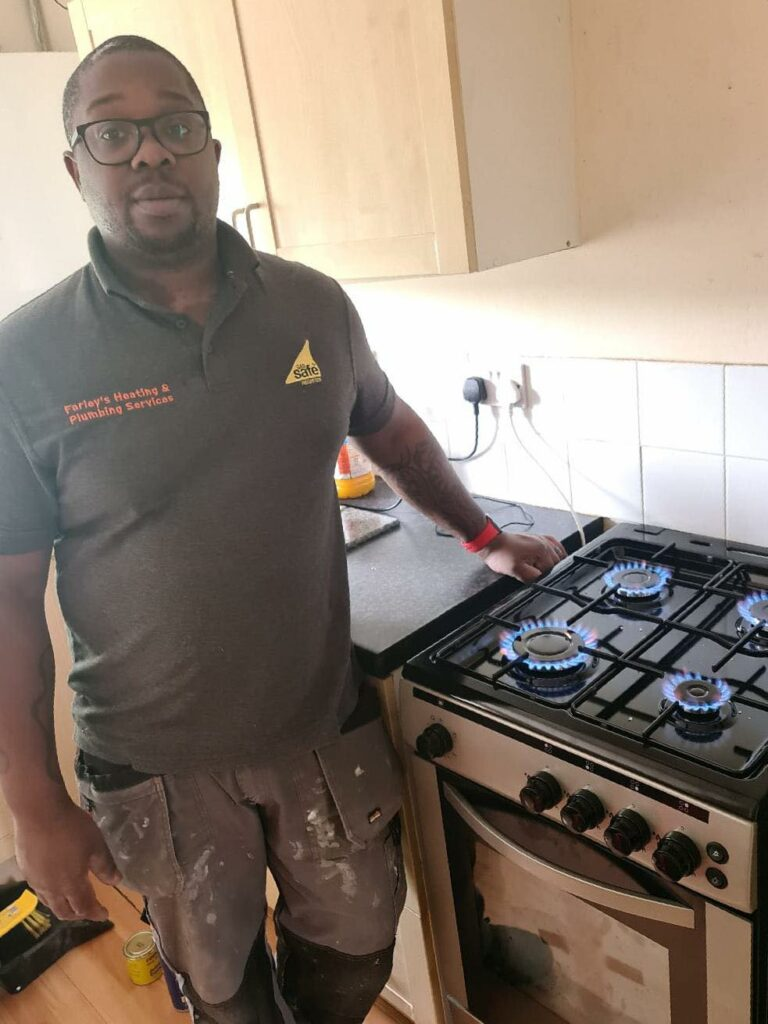 A smiling gas fitter standing by a gas cooker with all 4 rings burning