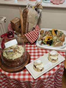 A photo of a Yorkshire welcome afternoon tea of sandwiches, scones and a cake set on a red and white tablecloth