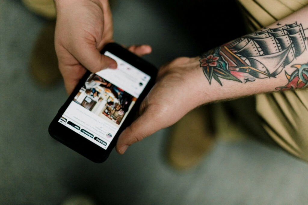 a pair of hands and tattooed forearms using social media on a mobile phone