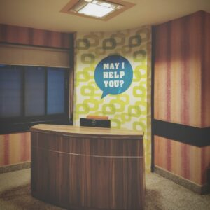 A hotel reception desk with a sign on the wall that says may I help you?