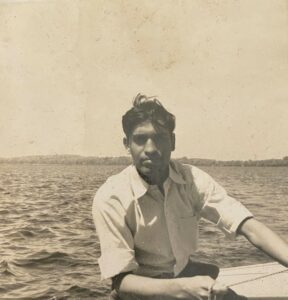 A black and white photo of Swati's Dad taken on a boat in 1958