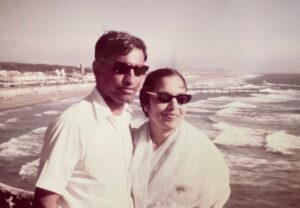 A photo of Swati's parents wearing sunglasses at the beach with the ocean behind them