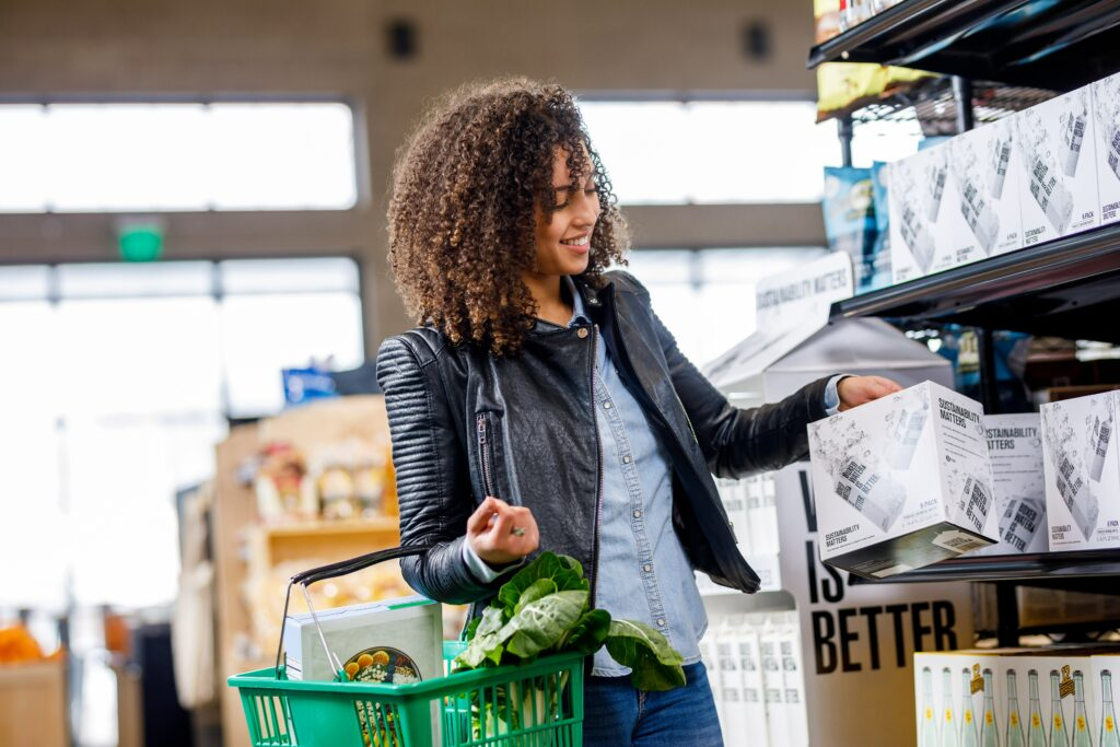 a person with curly hair carrying a shopping basket and taking a box down from a shelf