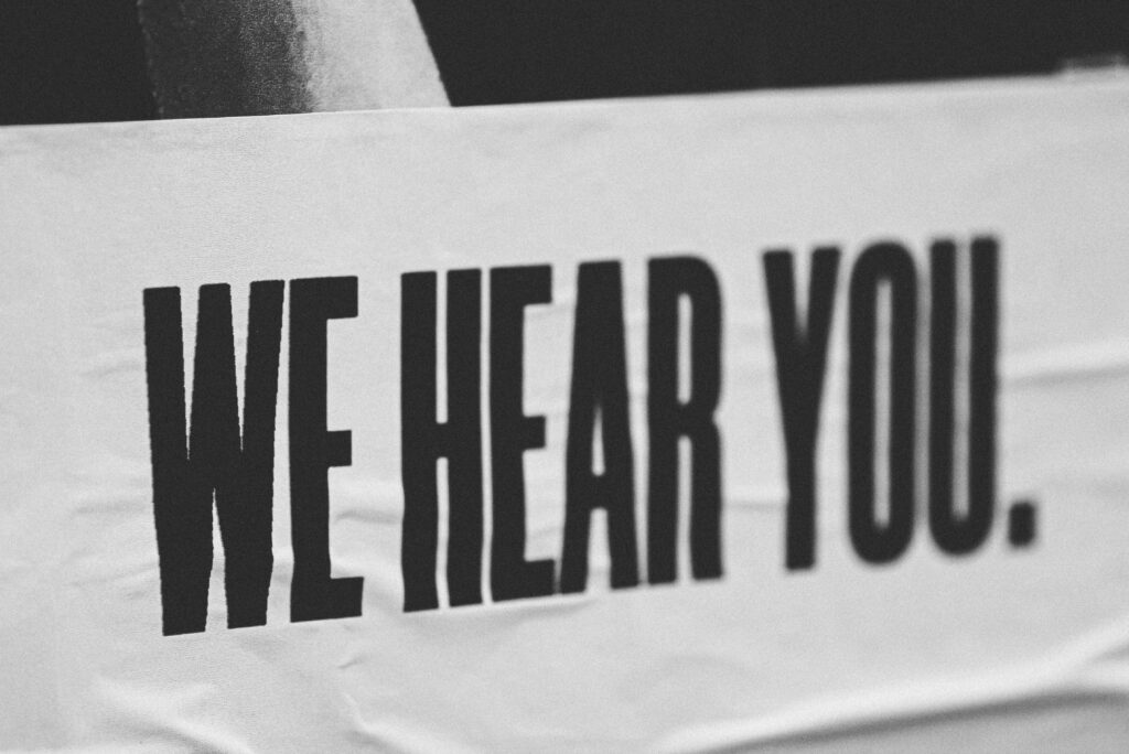 a black and white banner with the customer service phrase 'We hear you' on it