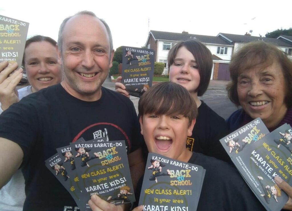 A selfie photo of a smiling family of grandma, mum, dad and 2 kids holding up leaflets for their karate club