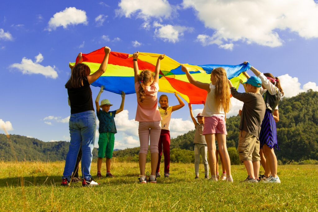 A group of primary education aged children standing in a circle and holding up a rainbow coloured parachute